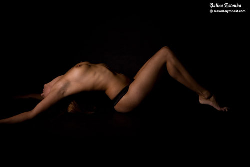 Naked gymnast girl bending in studio
