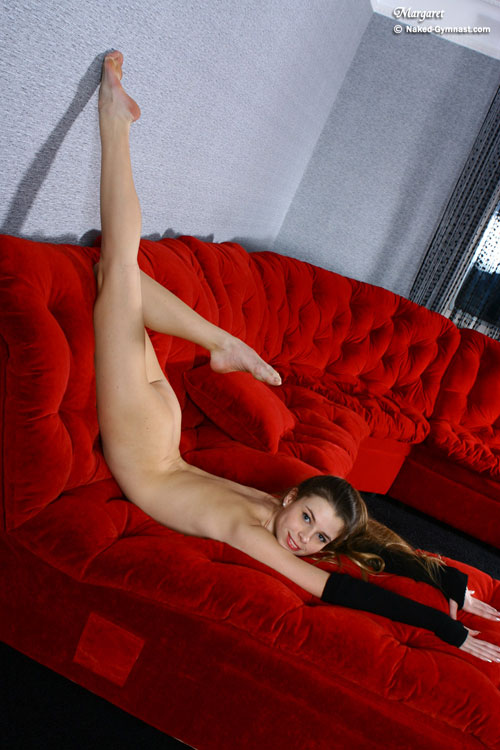 Flexible nude gymnast girl stretching on the sofa